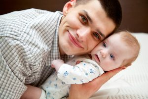 Adorable baby and father in home